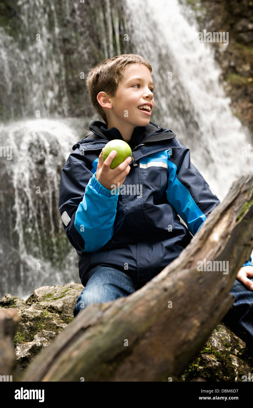 Boy Holding An Apple In Front Of Waterfall, Bavaria, Germany, Europe - Stock Image