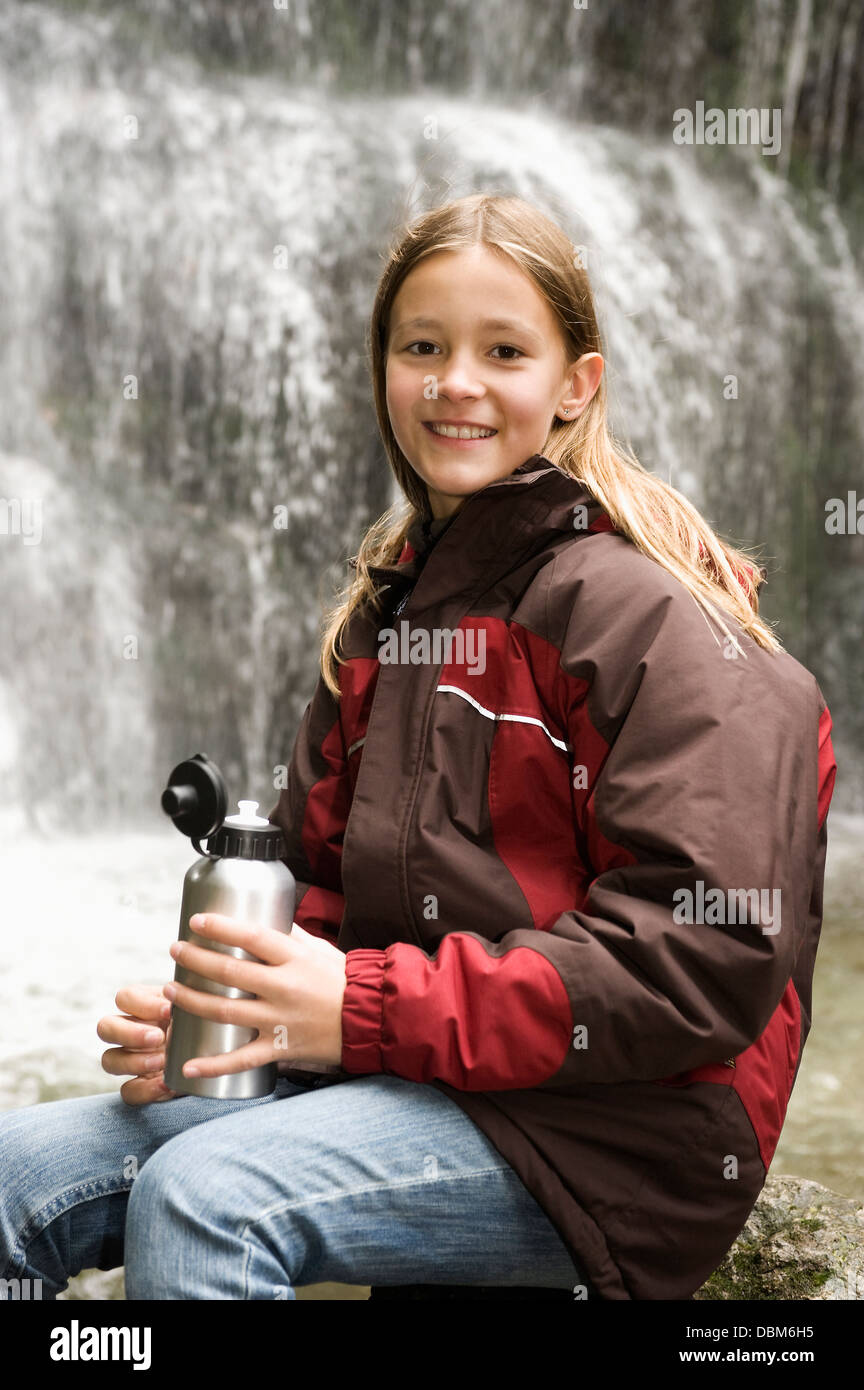 Girl With Thermos Bottle In Front Of A Waterfall, Bavaria, Germany, Europe - Stock Image