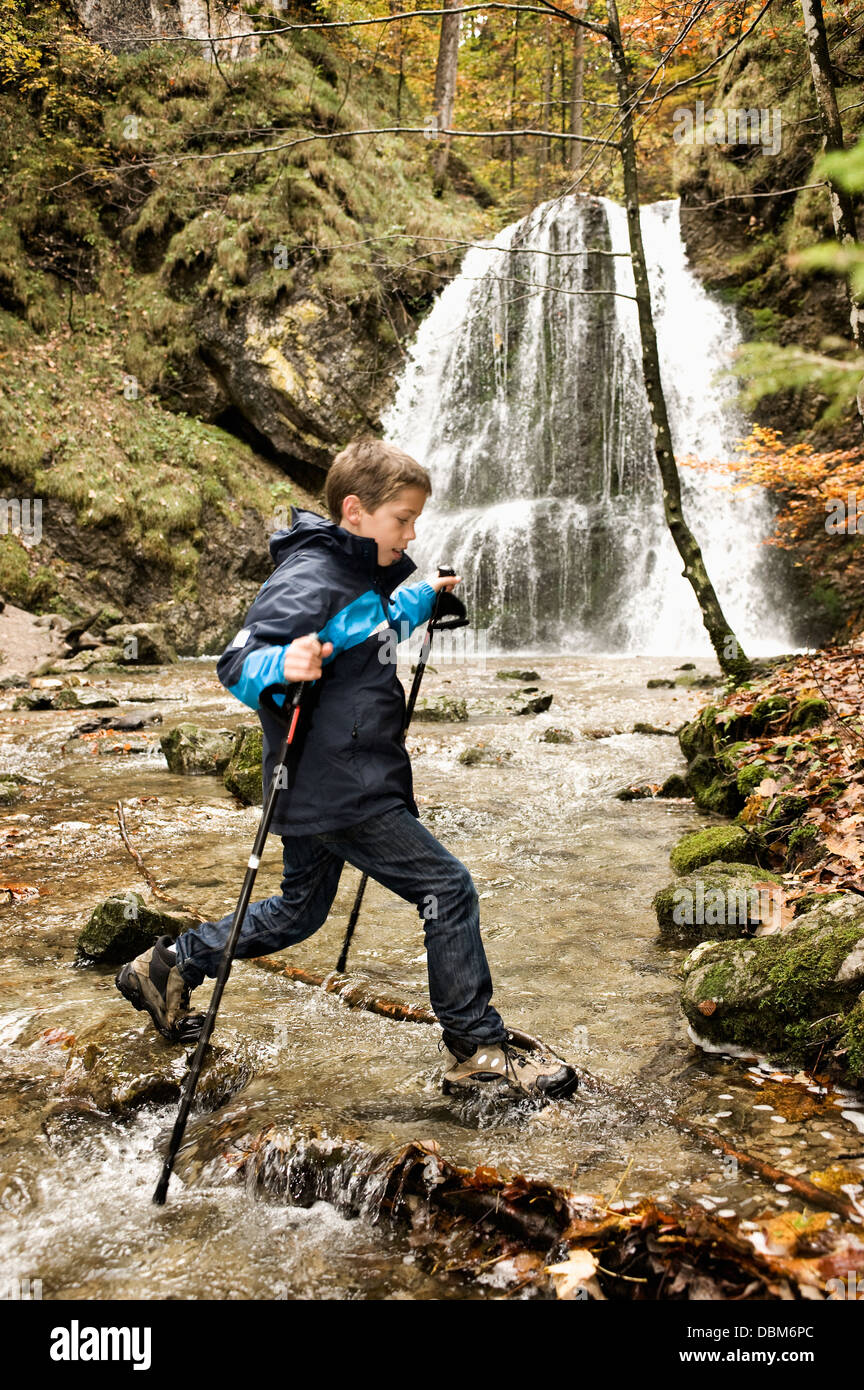 Nordic Walking, Boy crossing brook, Bavaria, Germany, Europe - Stock Image