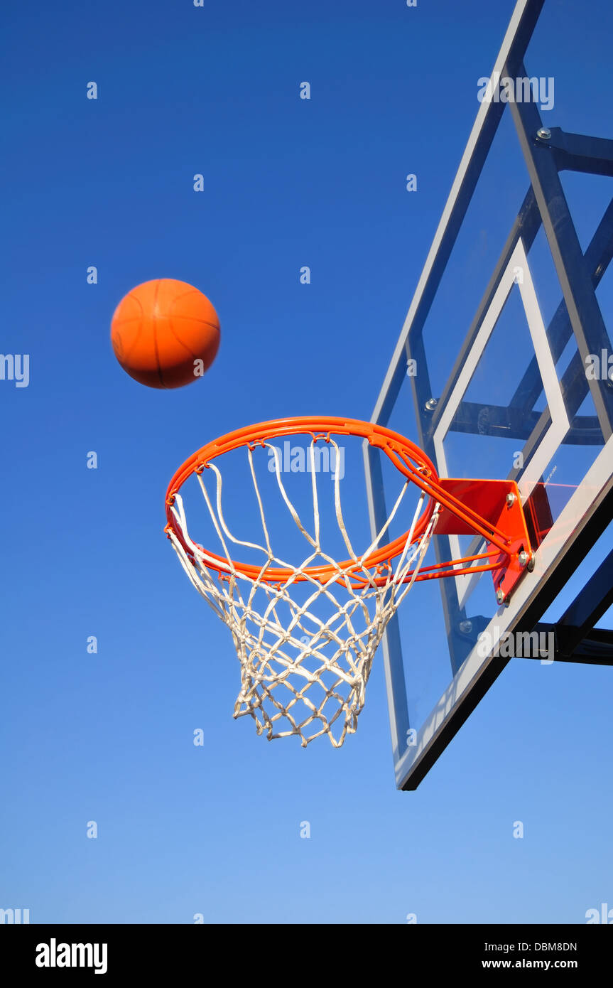 Basketball hoop against a blue sky will ball going into the net - Stock Image
