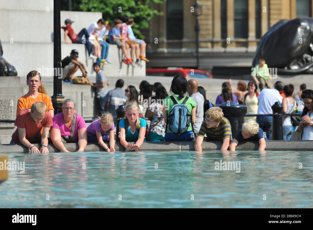 Trafalgar Square, London, UK. 1st August 2013. Children cool their hands in the fountains of Trafalgar Square in - Stock Image