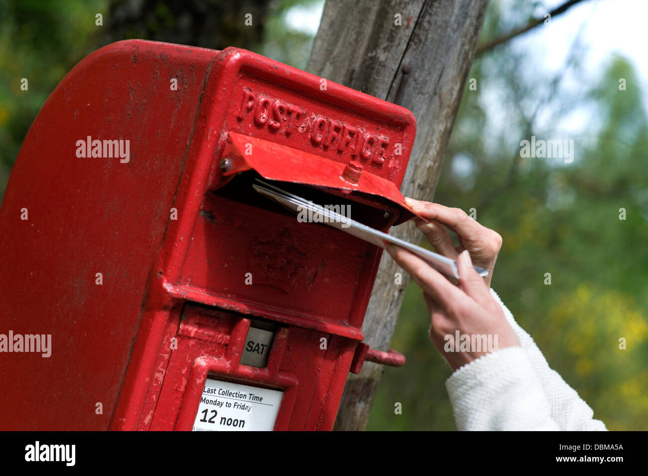 Posting a letter into a post box with anti bird nesting cover - Stock Image