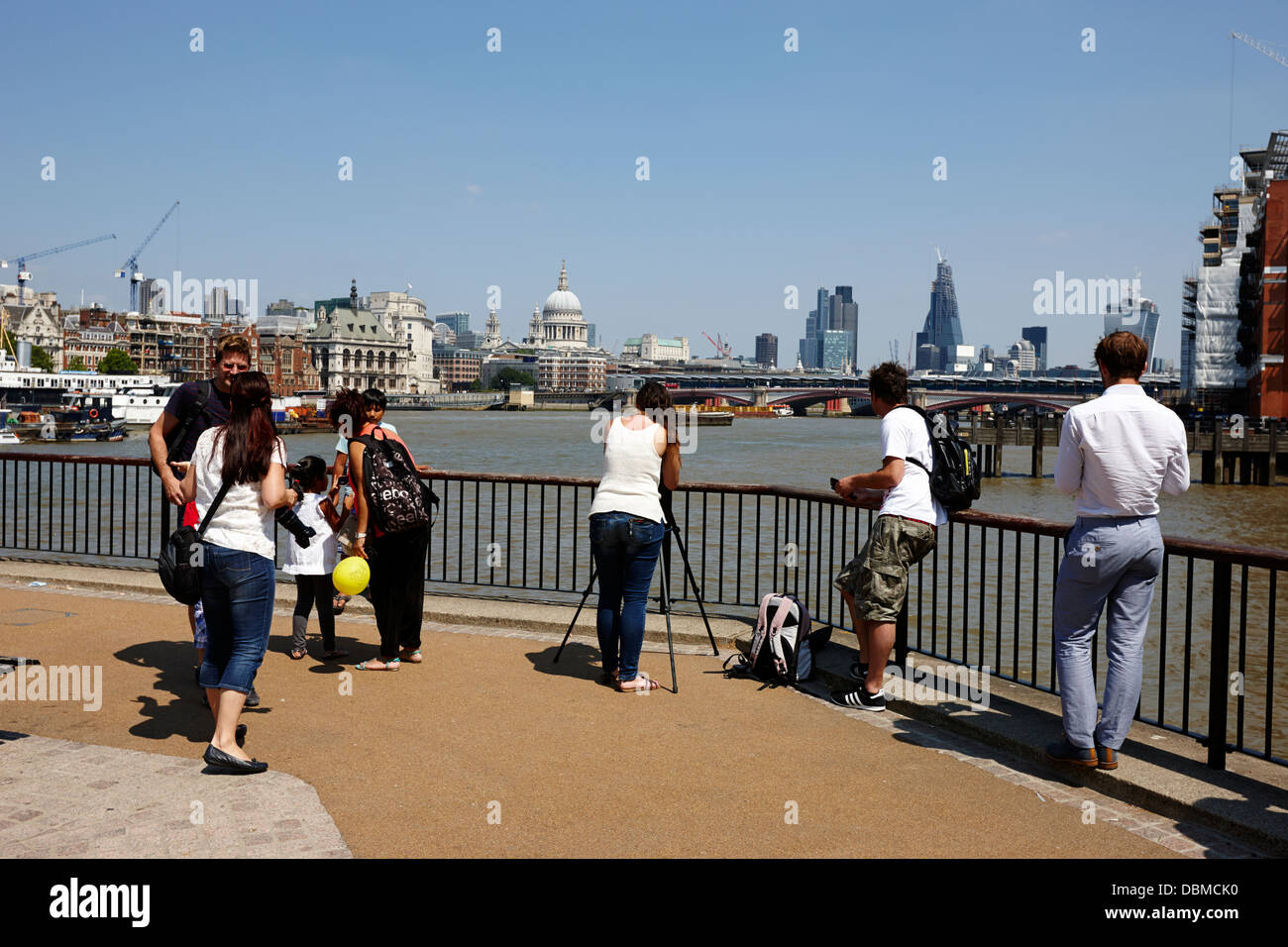 tourists taking photos at viewpoint on the south bank of the river thames London England UK - Stock Image