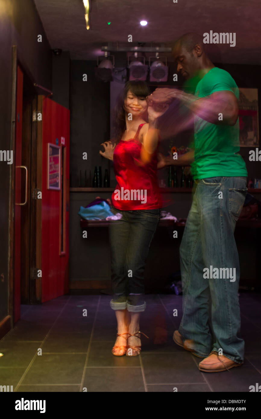 black man and chinese woman dancing salsa in a colourful bar stock