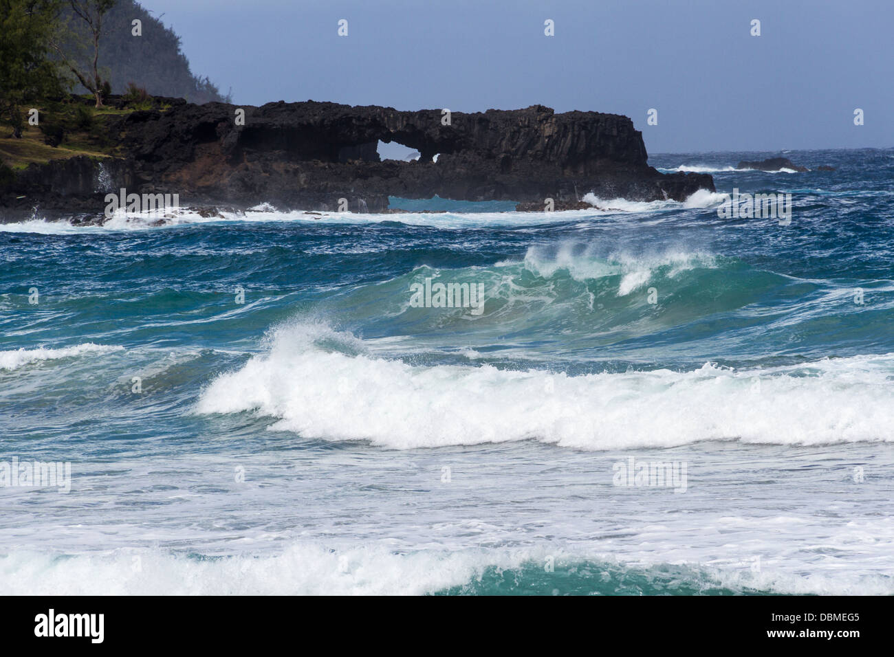 Arches and crashing waves at Kaihalulu Red Sand Beach on Maui - Stock Image