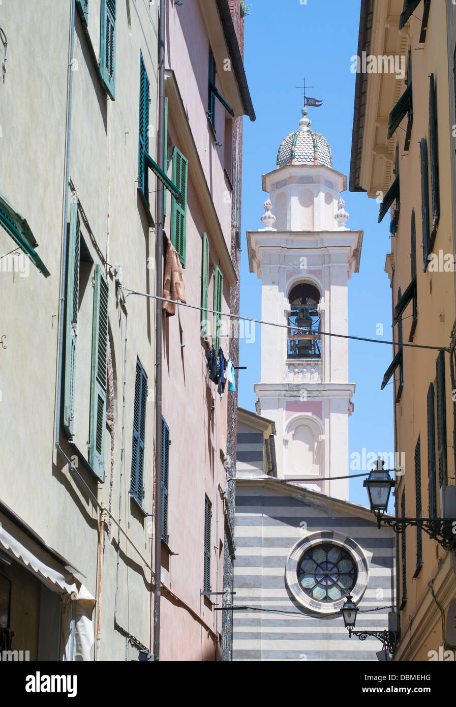 Bell tower of St Maria church seen along a narrow street within the historic northern Italian town of Albenga. - Stock Image