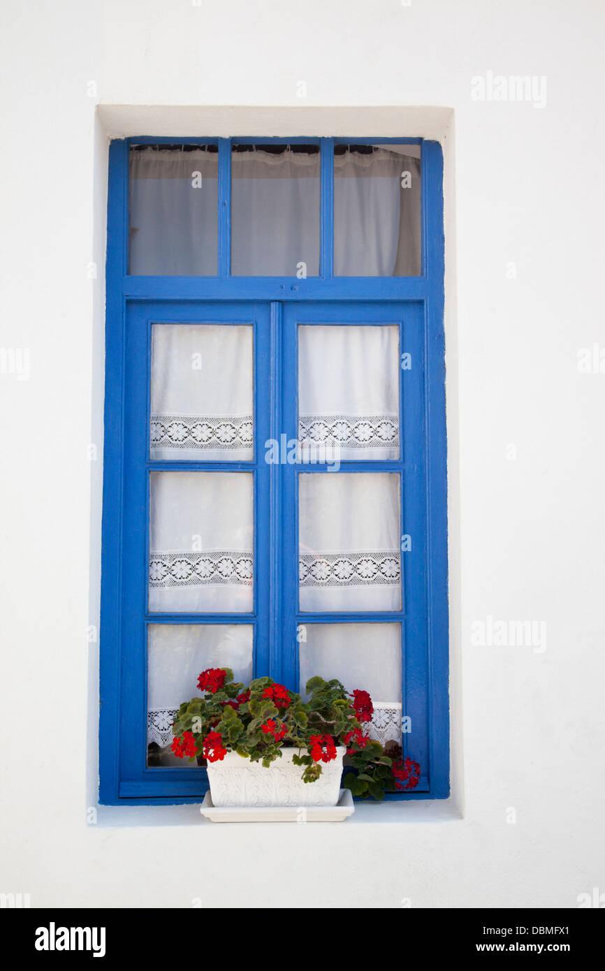 A pretty blue framed window in Mandraki, Nisyros, Greece - Stock Image