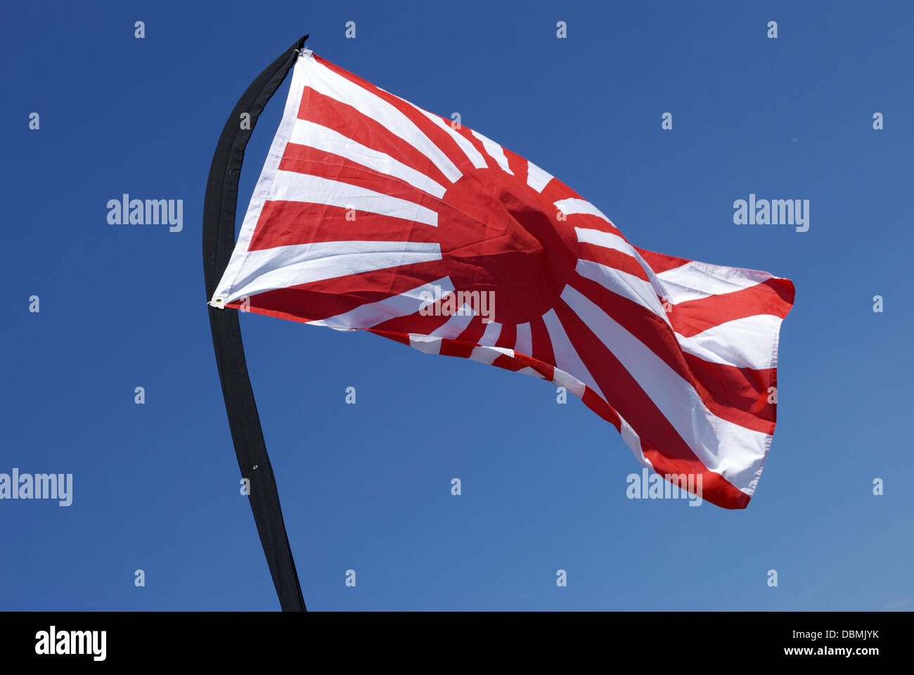 Rising sun flag wavering and fluttering movement on blue sky on windy day - Stock Image