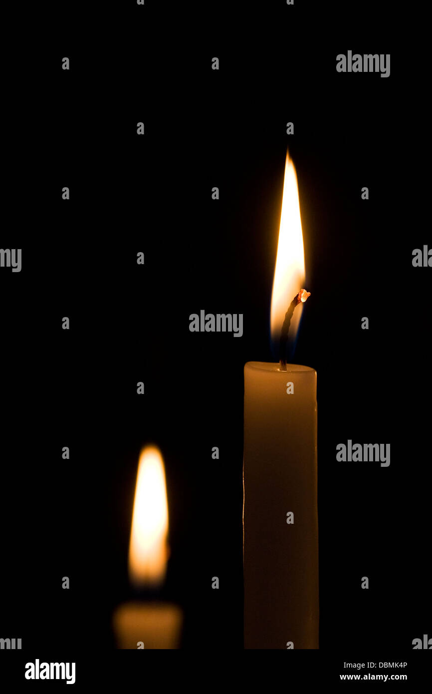 Two candles in the darkness. - Stock Image