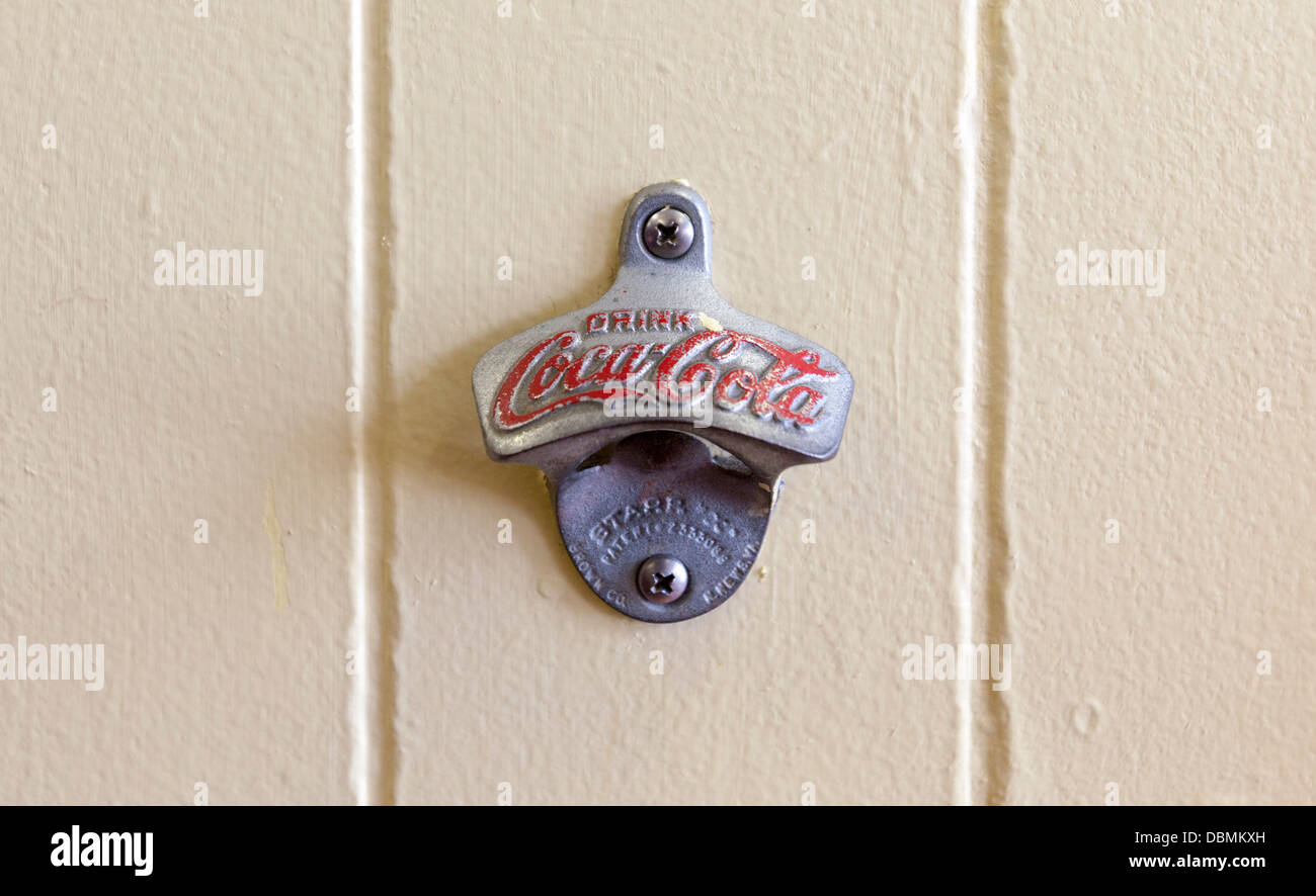 Closeup of an antique soda bottle opener mounted on a wall. - Stock Image