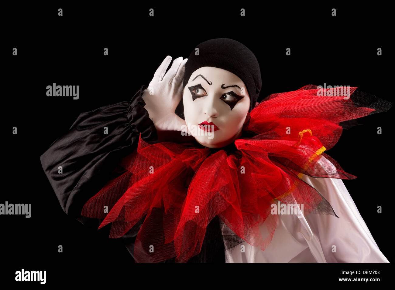 Mime Pierrot actor holding her hands as in listening - Stock Image