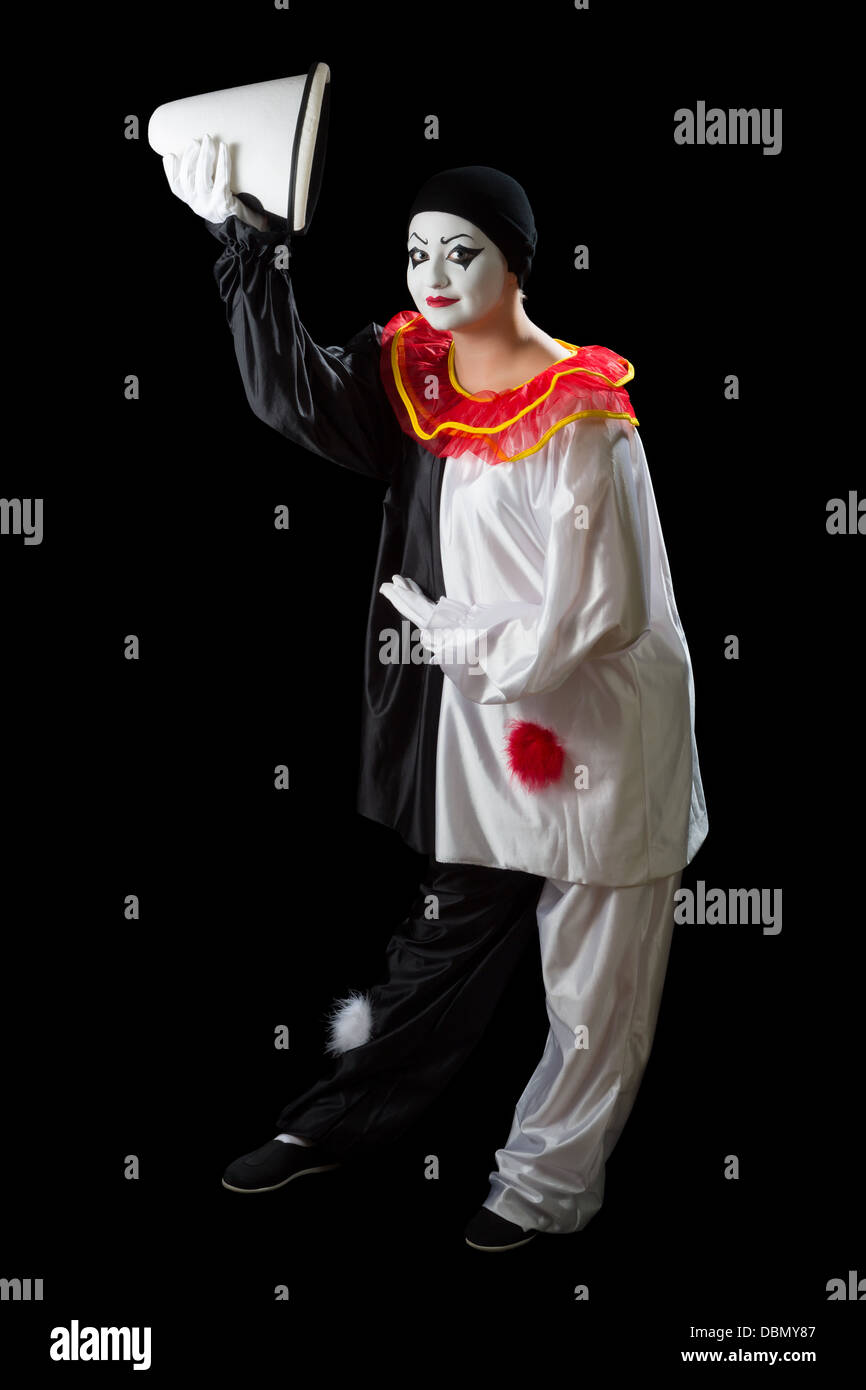 Mime Pierrot isolated on black greeting with her hat - Stock Image