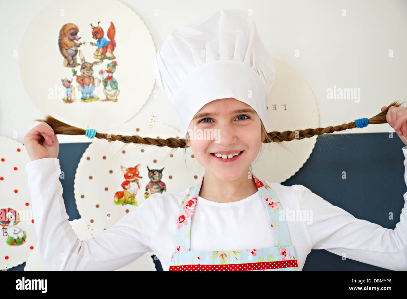 Little girl with chef's hat fooling around with her pigtails, Munich, Bavaria, Germany - Stock Image