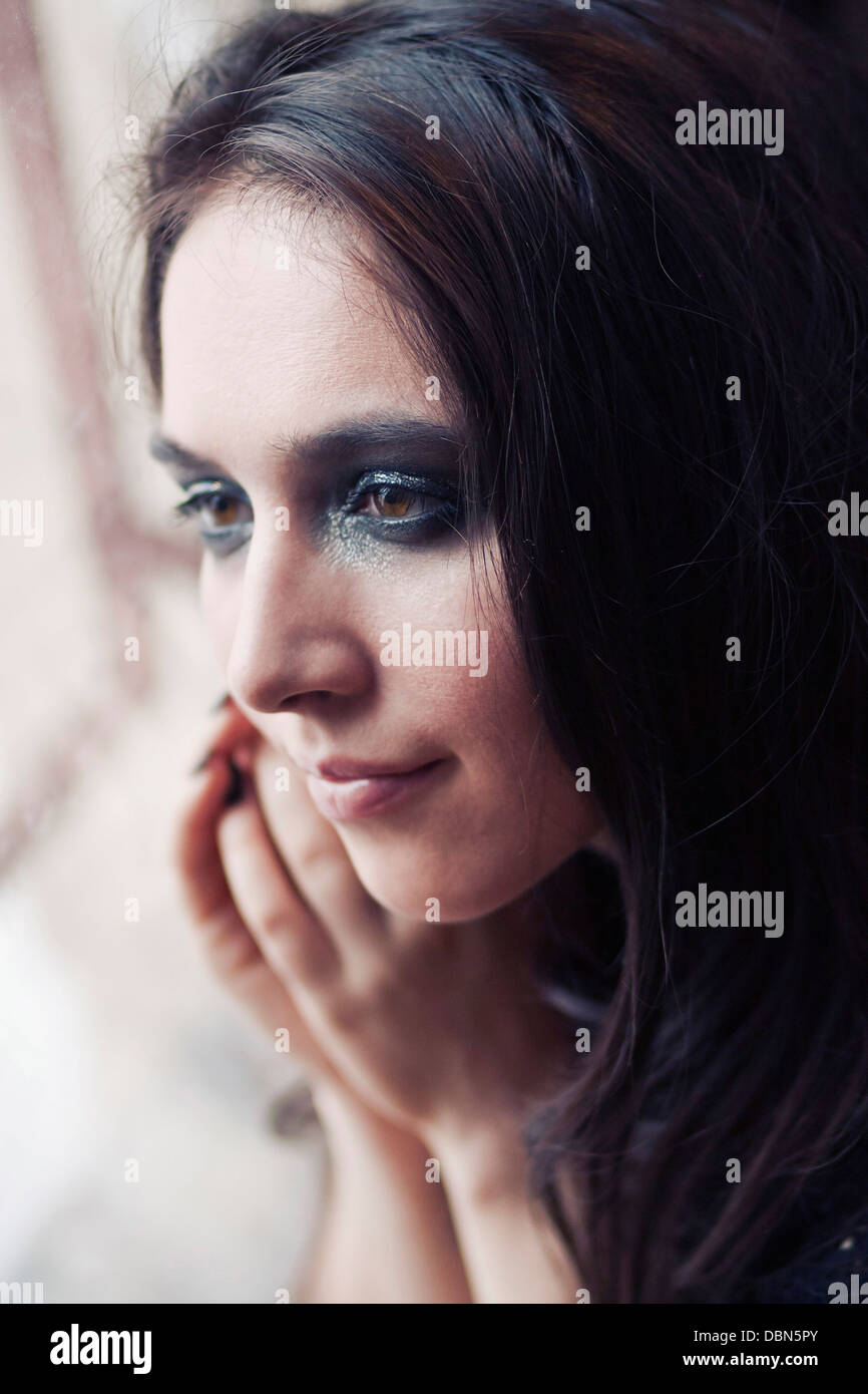 Young woman with long hair looking through window, Zagreb, Croatia, Europe Stock Photo