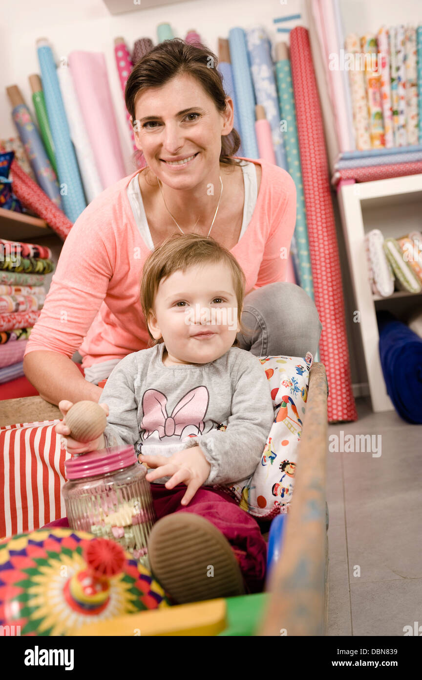 Mother With Baby Girl In Shop, Munich, Bavaria, Germany, Europe - Stock Image