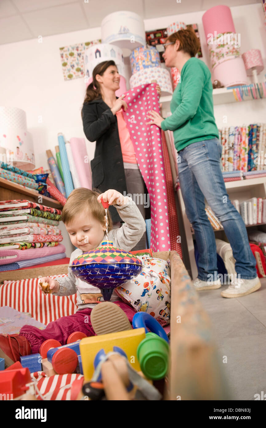 Women In A Shop, Baby Girl Playing in Foreground, Munich, Bavaria, Germany, Europe - Stock Image