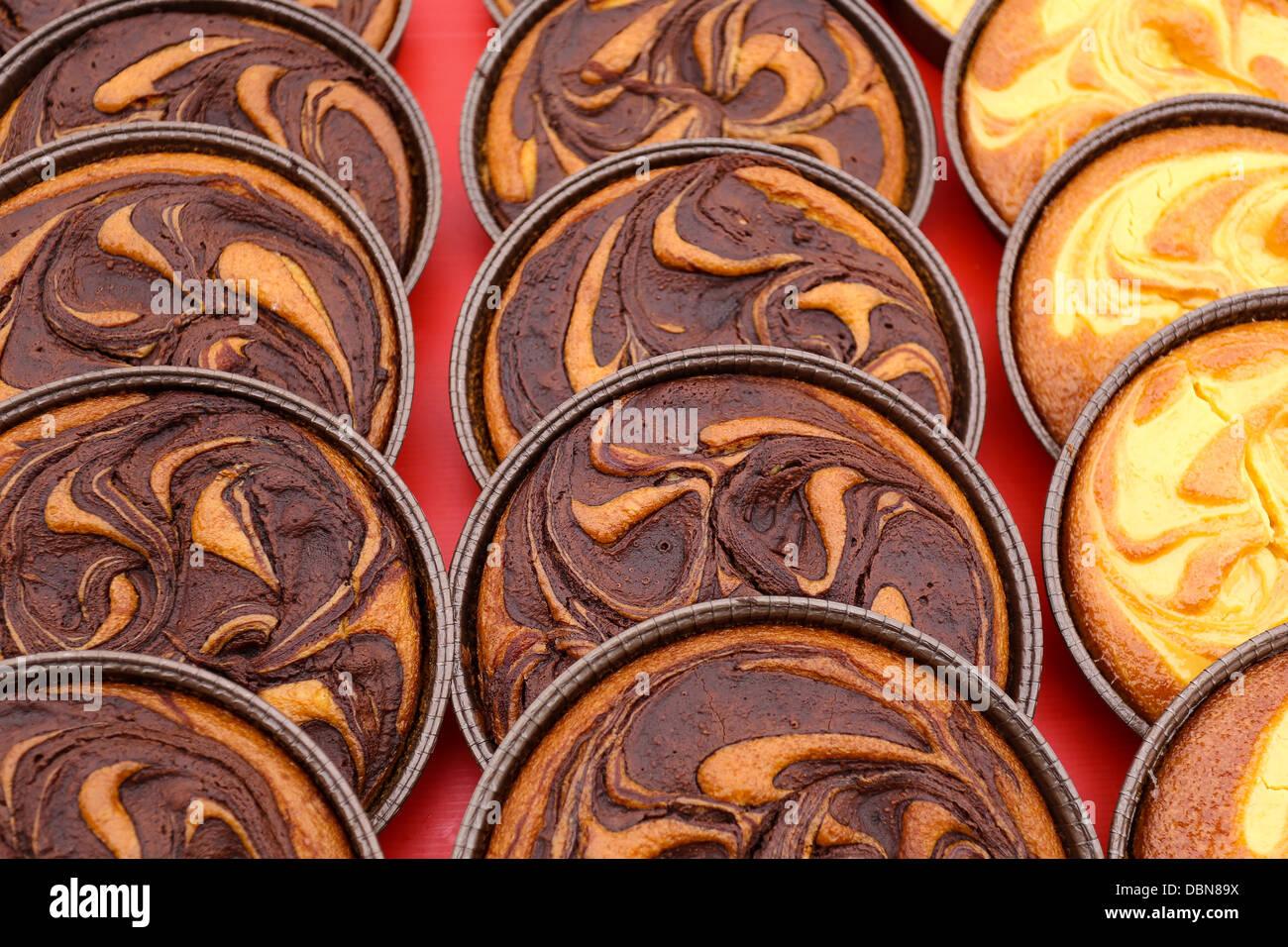 Chocolate tarts and Custard cream tarts on display - Stock Image