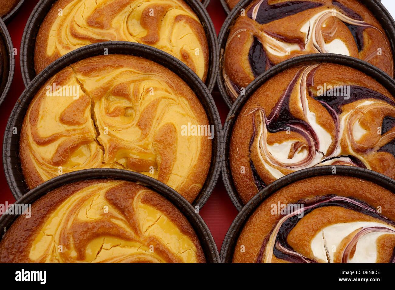 Custard cream tarts and Raspberry tarts on display - Stock Image