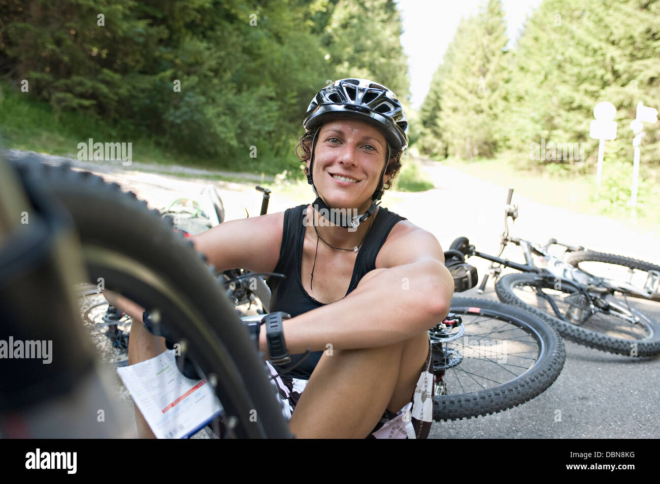 Female Bicyclist Sitting On Road, Sonthofen, Schattwald, Bavaria, Germany - Stock Image