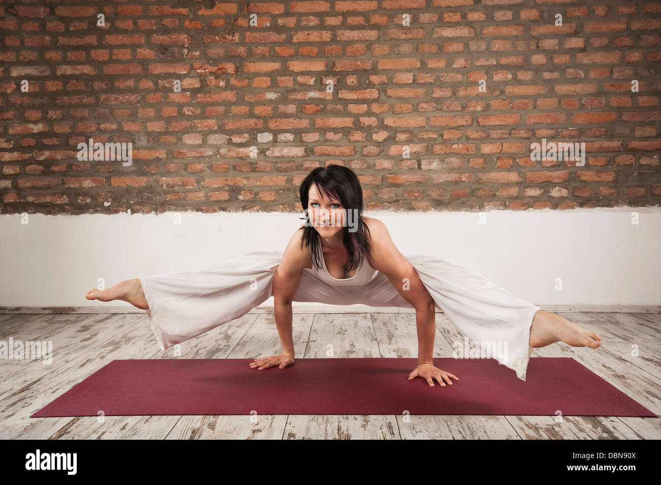 Young Woman practising Yoga, side crow pose - Stock Image