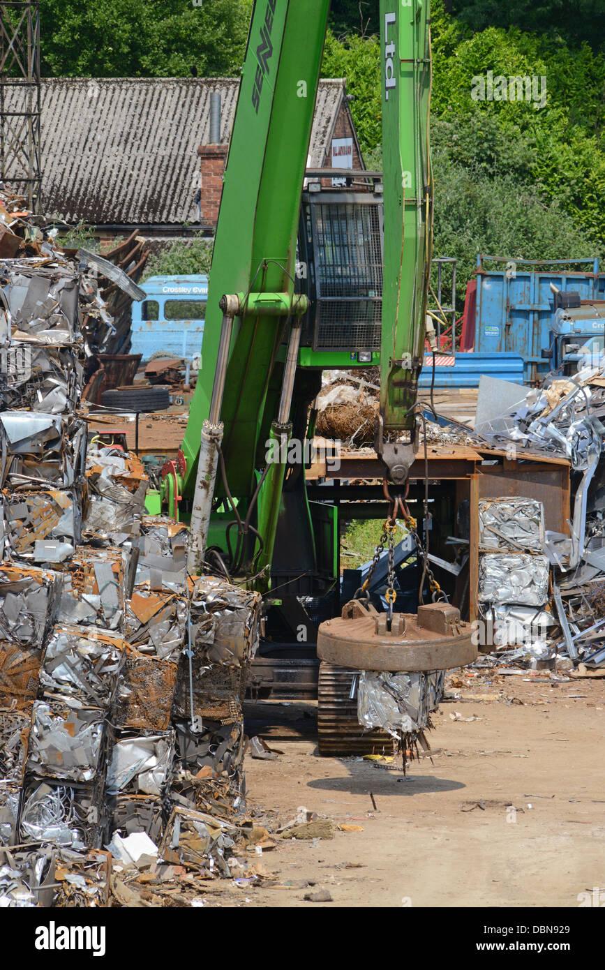 magnetic grab on crane lifting metal bale at scrapyard united kingdom - Stock Image