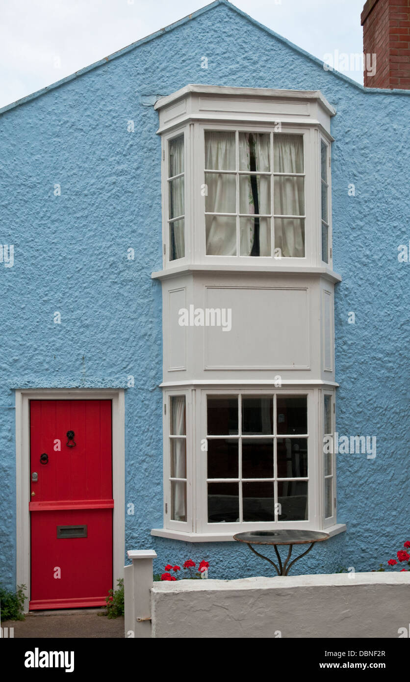 Portrait image of a small blue house with a red front door. - Stock Image