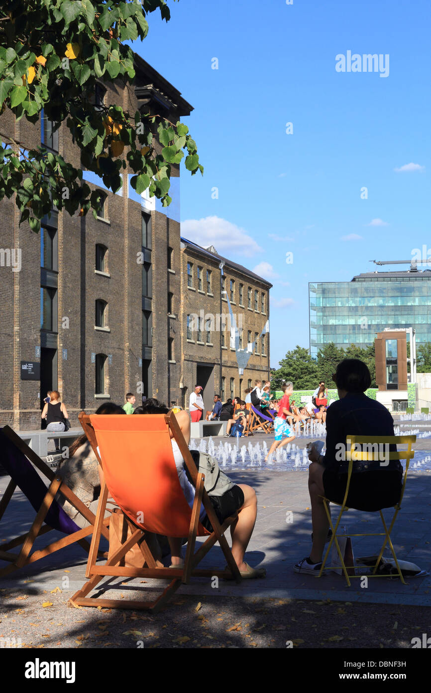 People relaxing on a warm, summer's evening on Granary Square, NC1, in the Kings Cross regeneration zone, in - Stock Image