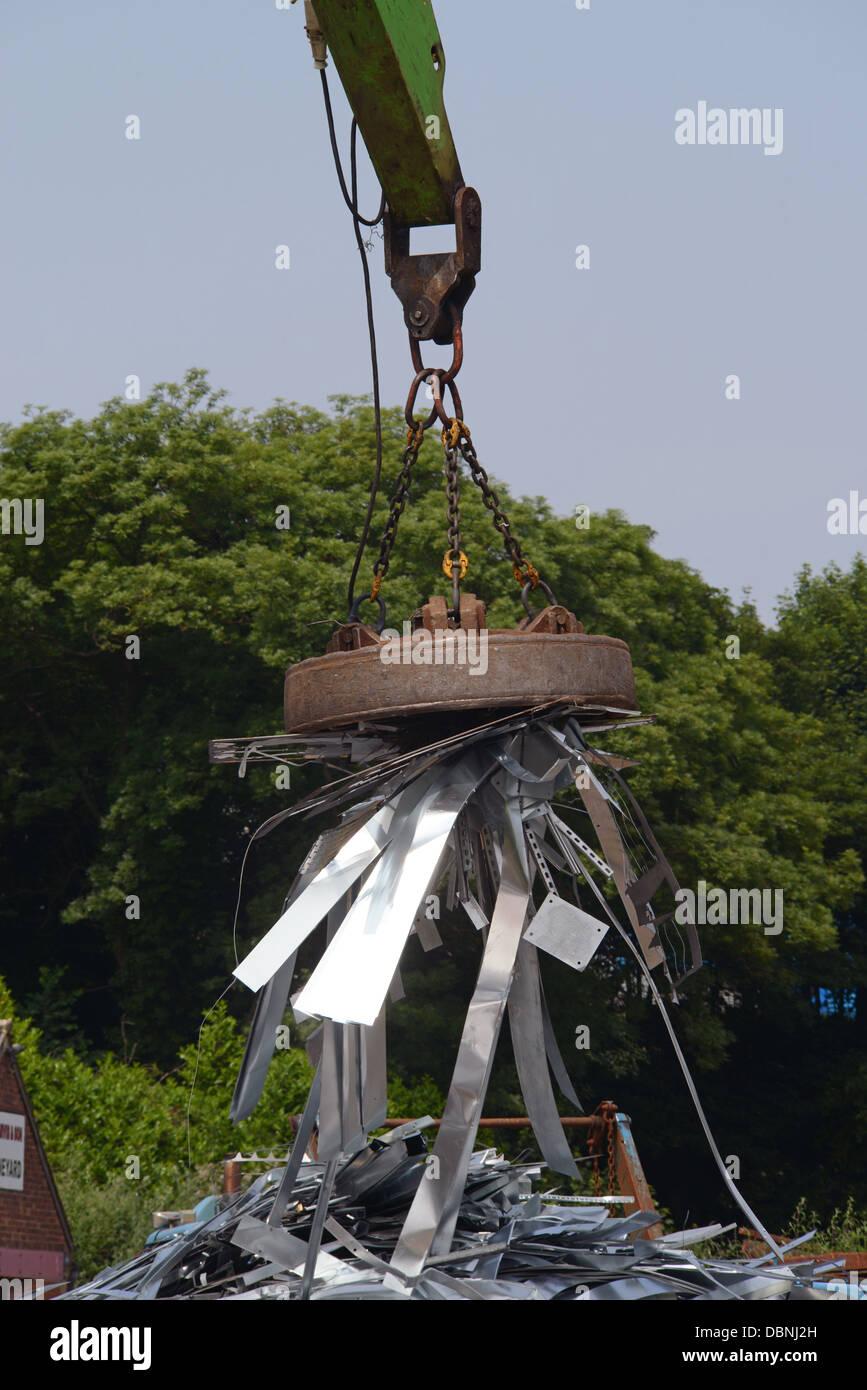 magnetic grab on crane lifting metal at scrapyard uk - Stock Image