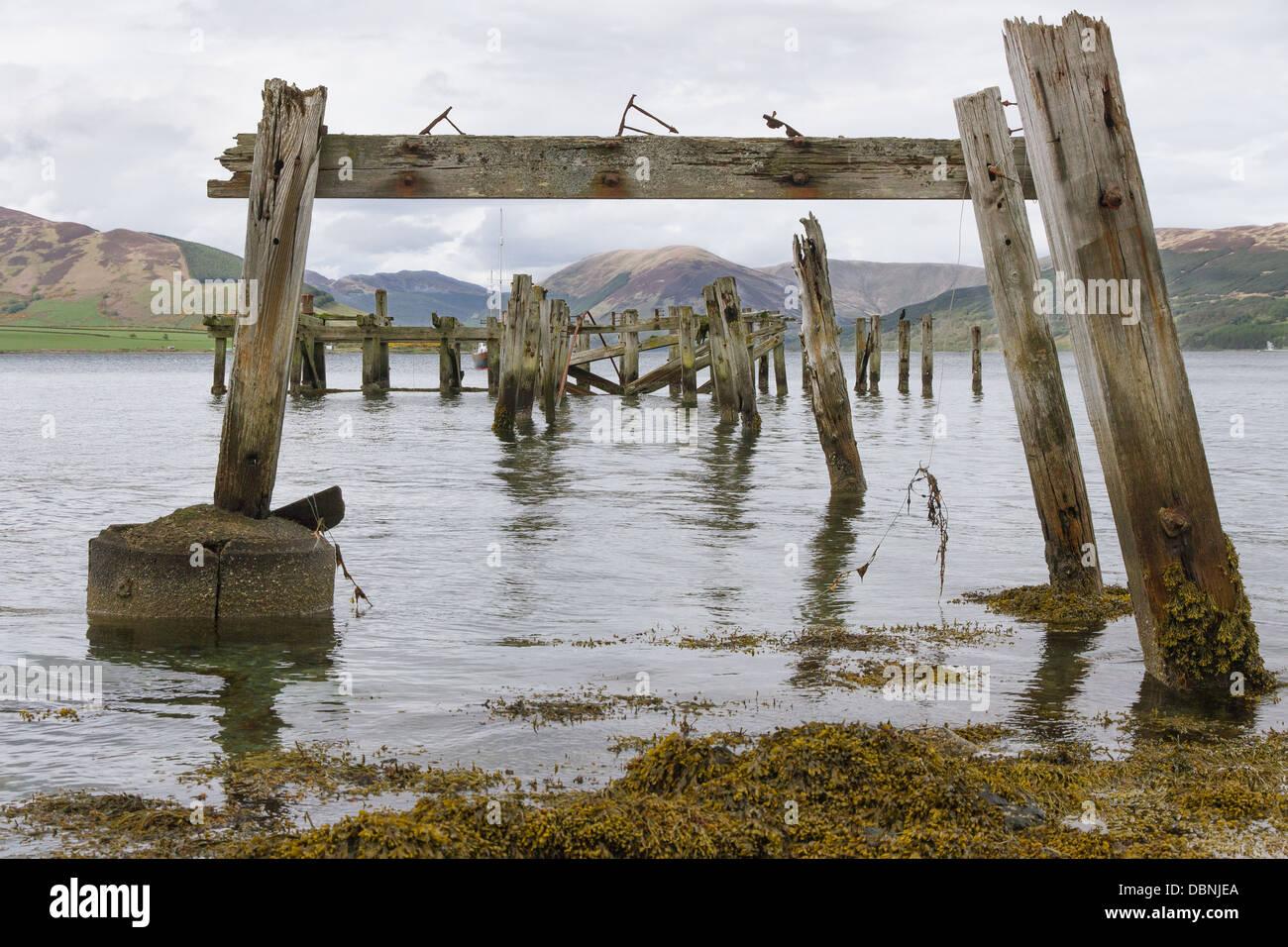 Looking through the the decrepit pier at Port Bannatyne, Isle of Bute out to highland mountains - Stock Image