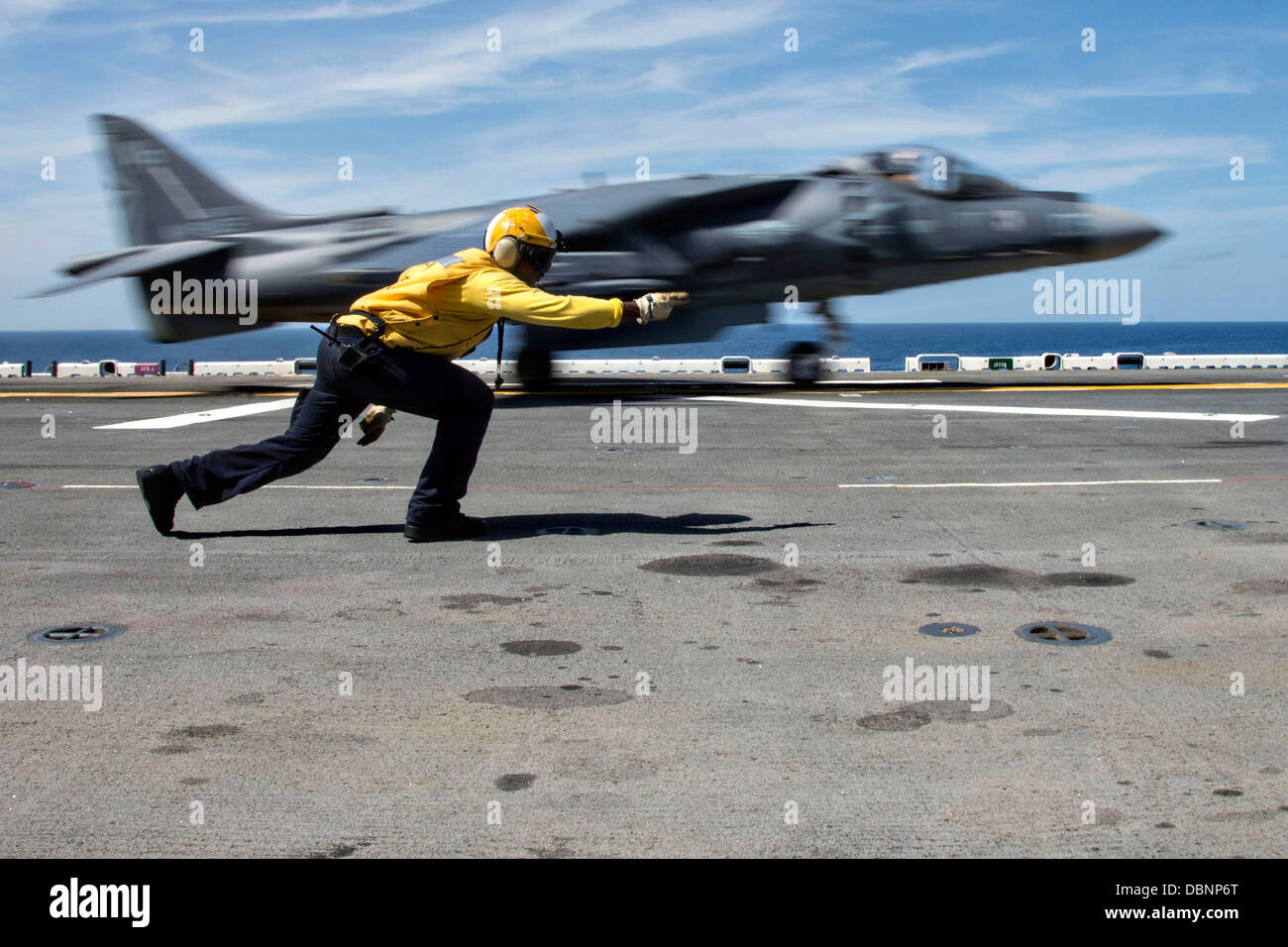 A US Navy Aviation Boatswain Mate signals a AV-8B II Harrier fighter jet to launch off the flight deck of the amphibious - Stock Image