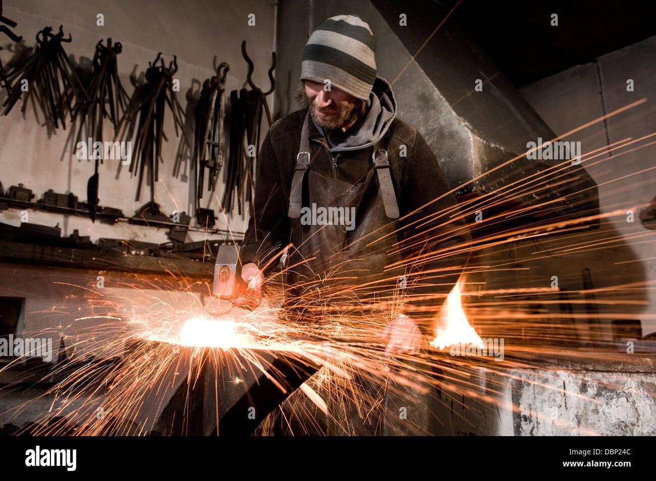 Blacksmith hammering metal on an anvil, Landshut, Bavaria, Germany - Stock Image