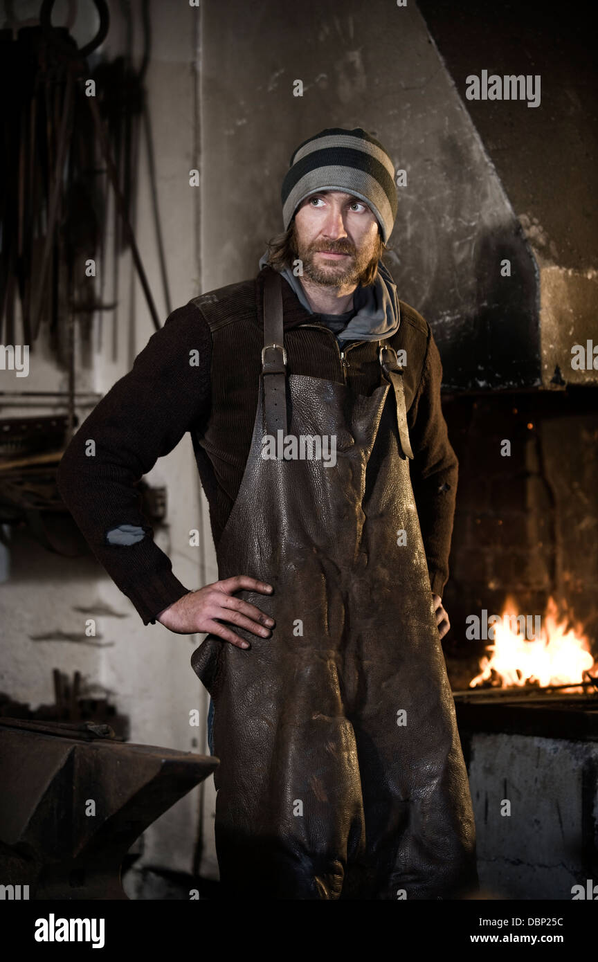 Blacksmith standing in workshop, forge in background, Landshut, Bavaria, Germany Stock Photo