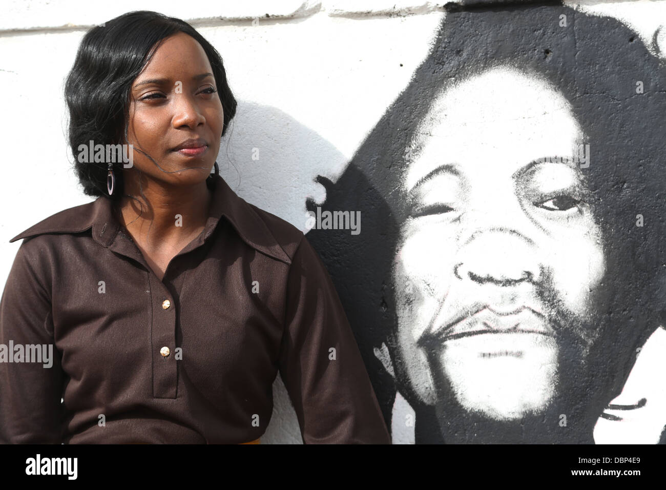 Musician Kamande poses for a picture on a wall with Dedan Kimathi's(Mau Mau Hero) painting. - Stock Image