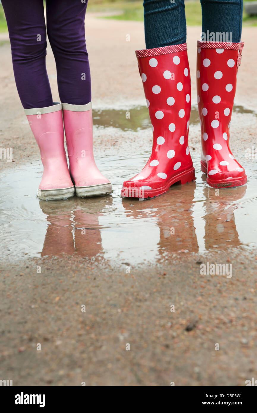 Girls (6-7, 12-13) wearing rubber boots standing in puddle - Stock Image