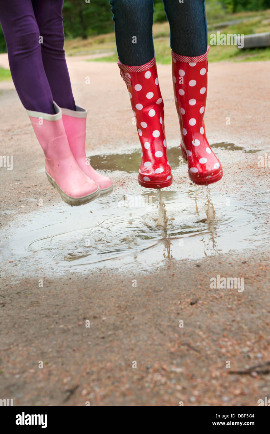 Girls (6-7, 12-13) wearing rubber boots jumping in puddle - Stock Image