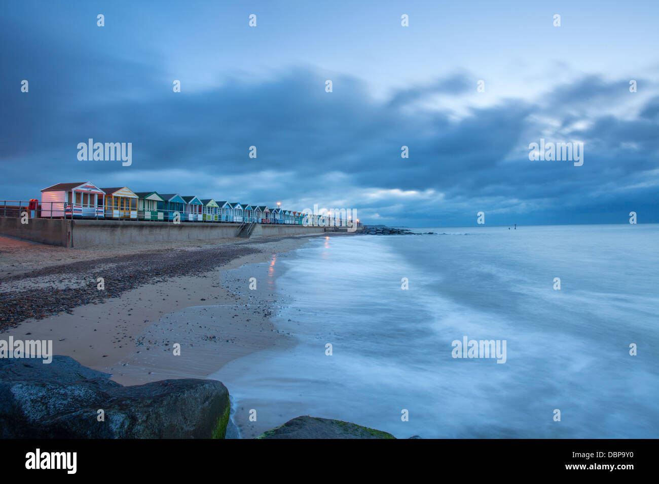 Beach waves and beach huts on promenade Southwold, Suffolk, UK - Stock Image