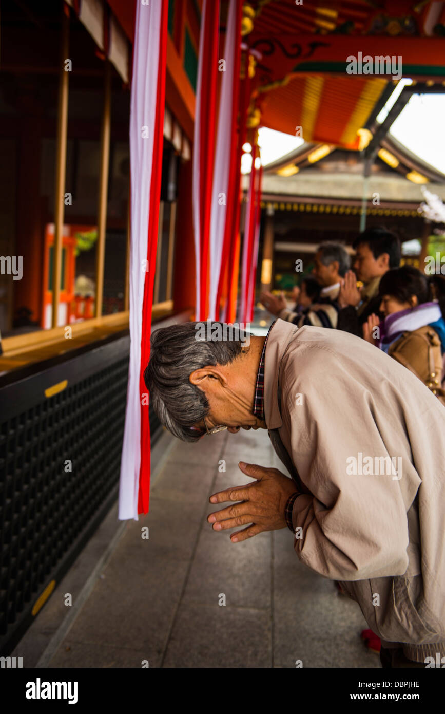 Praying pilgrim in the Endless Red Gates of Kyoto's Fushimi Inari Shrine, Kyoto, Japan, Asia - Stock Image