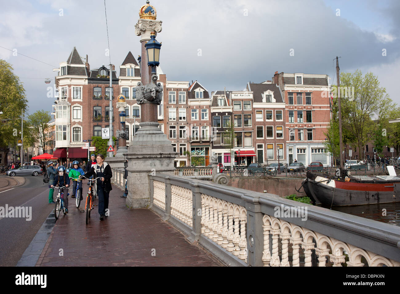 Sidewalk on Hogesluis Bridge (Hoge Sluis Brug) and historic houses, city of Amsterdam in Holland, Netherlands. - Stock Image