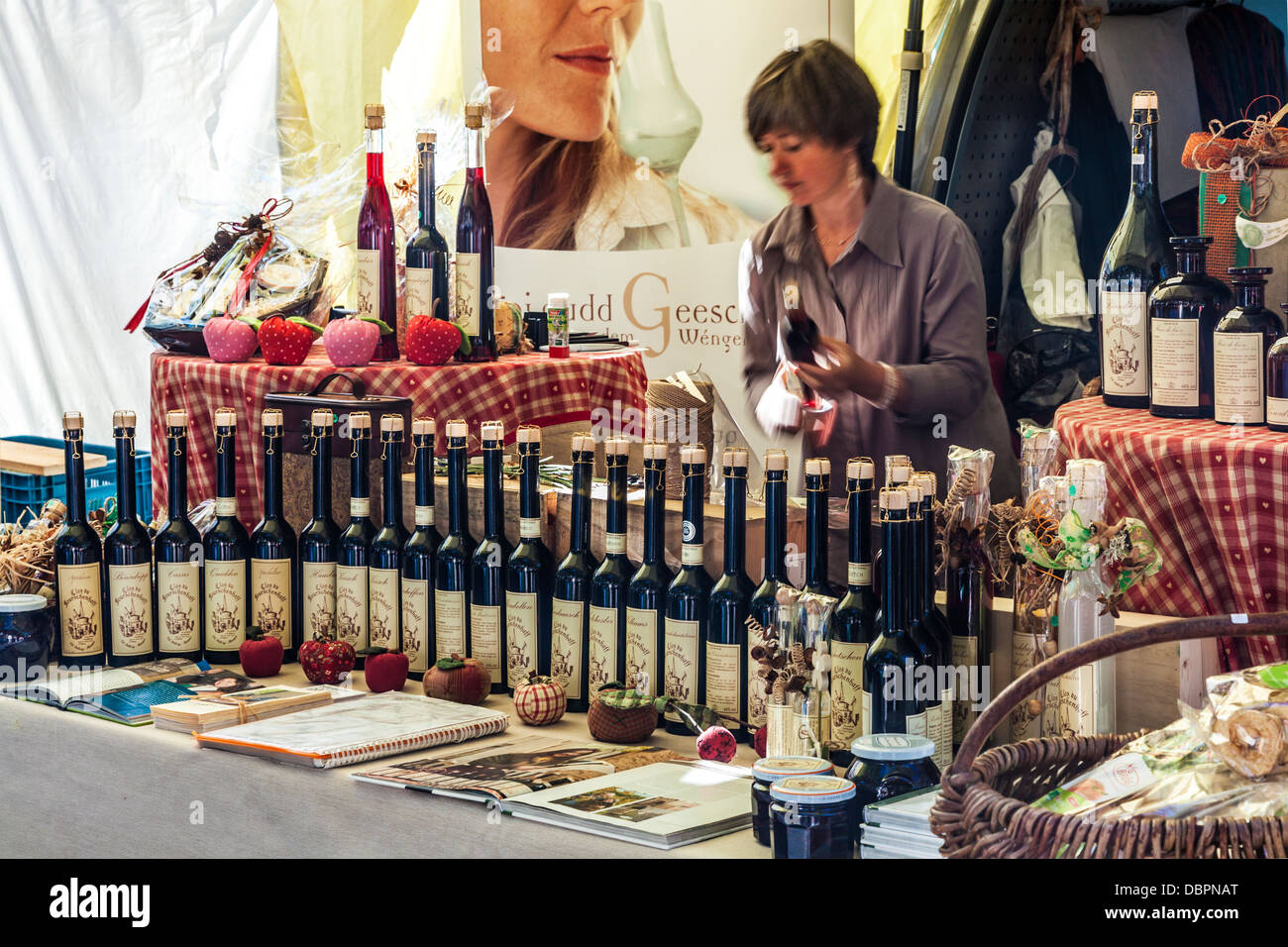 A stall selling a range of clear fruit brandies known as 'eau de vie' at the market in the Place Guillaume - Stock Image