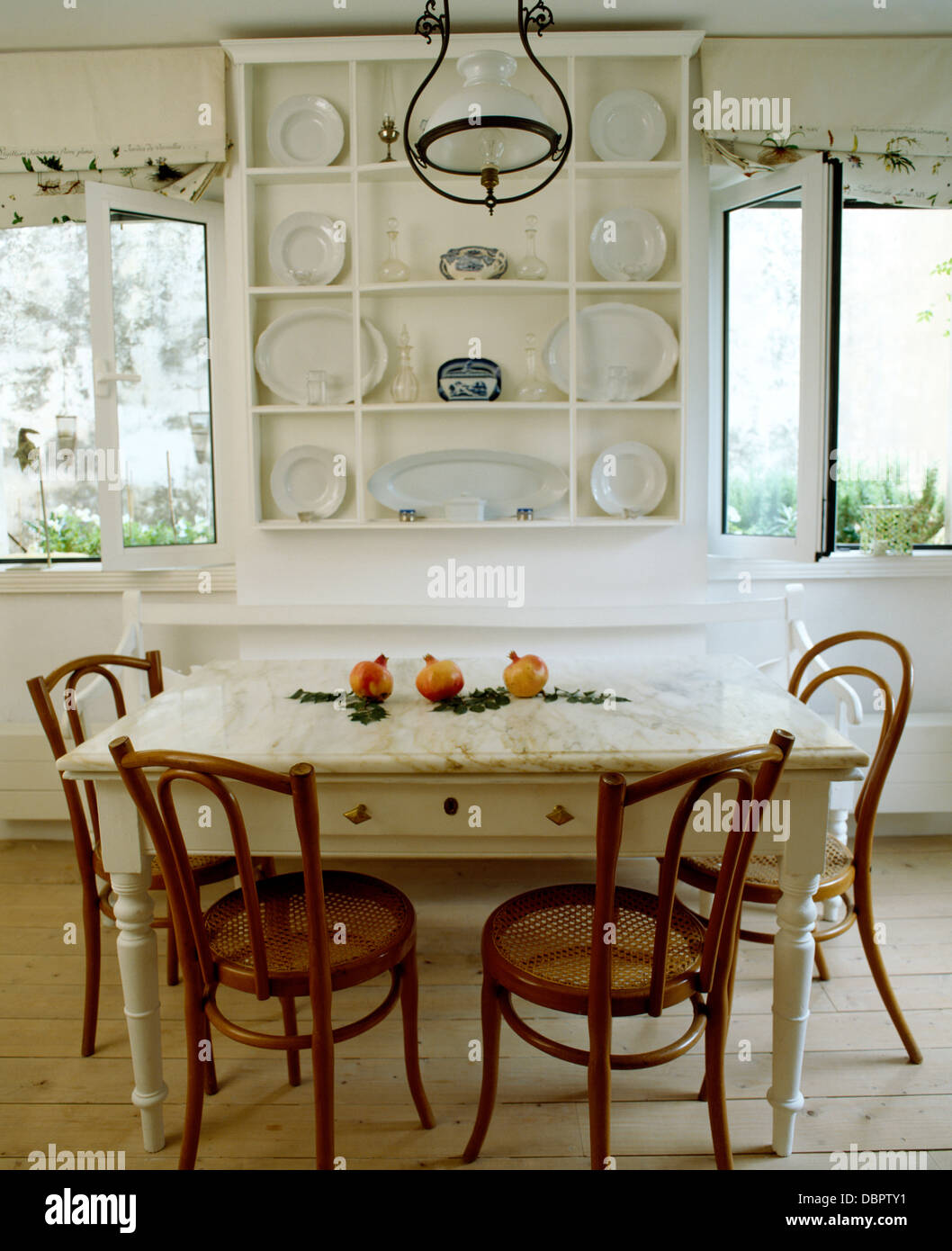 Simple White Shelves And Painted Table With Old Bentwood Chairs In White  Coastal Dining Room With Wooden Floor