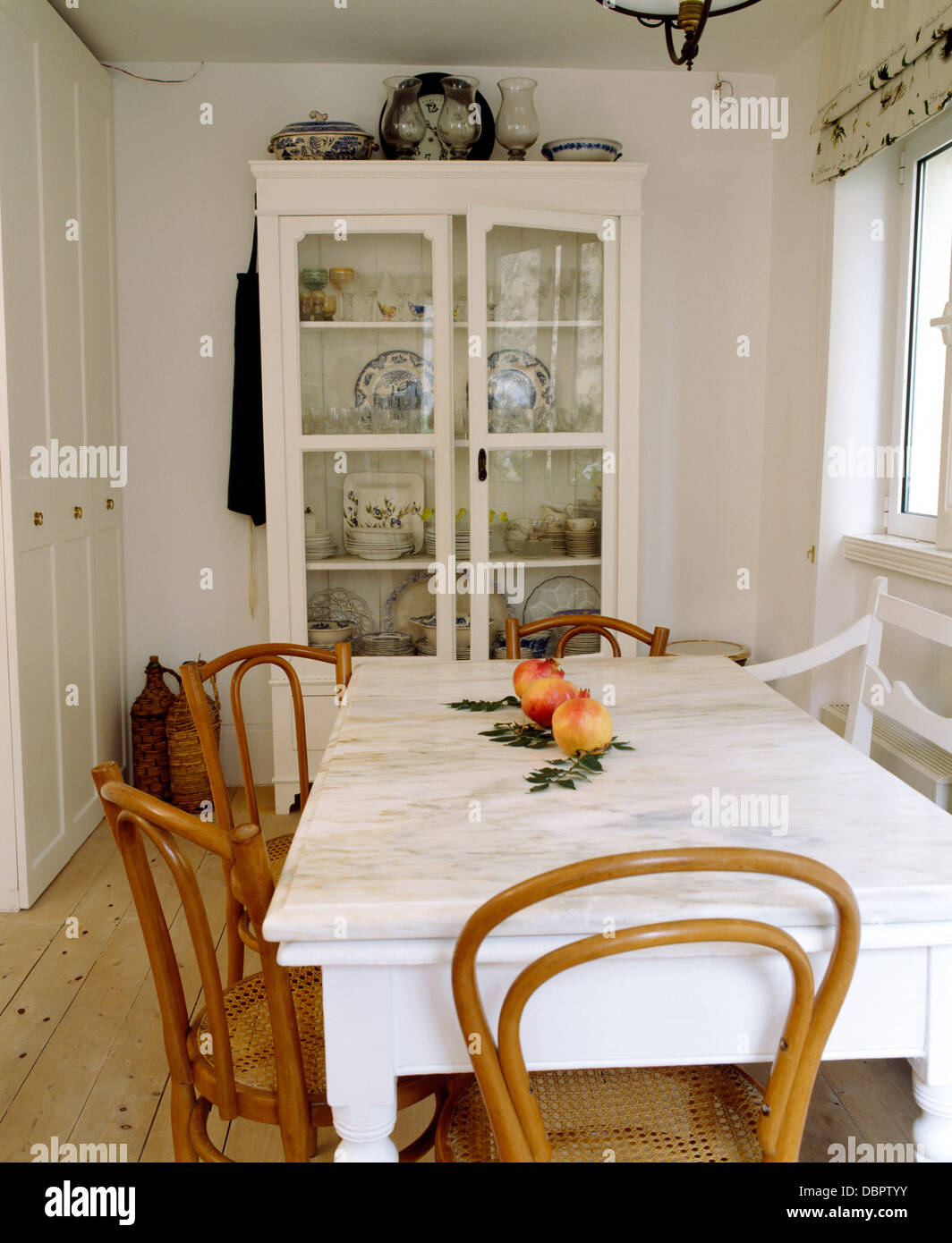 Marble-topped painted table with antique Bentwood chairs in white coastal  dining room with white glass-front cupboard - Marble-topped Painted Table With Antique Bentwood Chairs In White