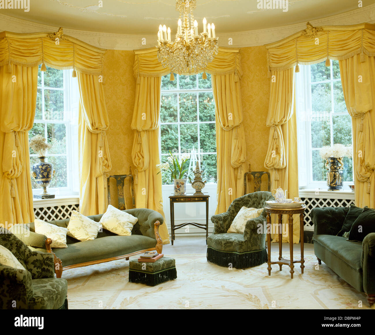 Yellow Swagged And Tailed Silk Curtains On Tall Windows In