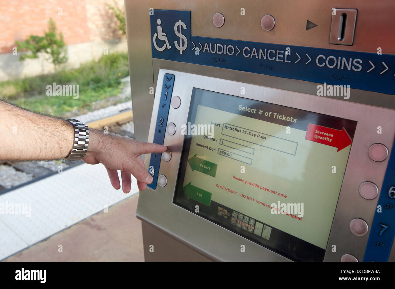 Morning commuter uses the Metro-Rail ticket payment kiosk at public transportation stations in Austin, Texas - Stock Image