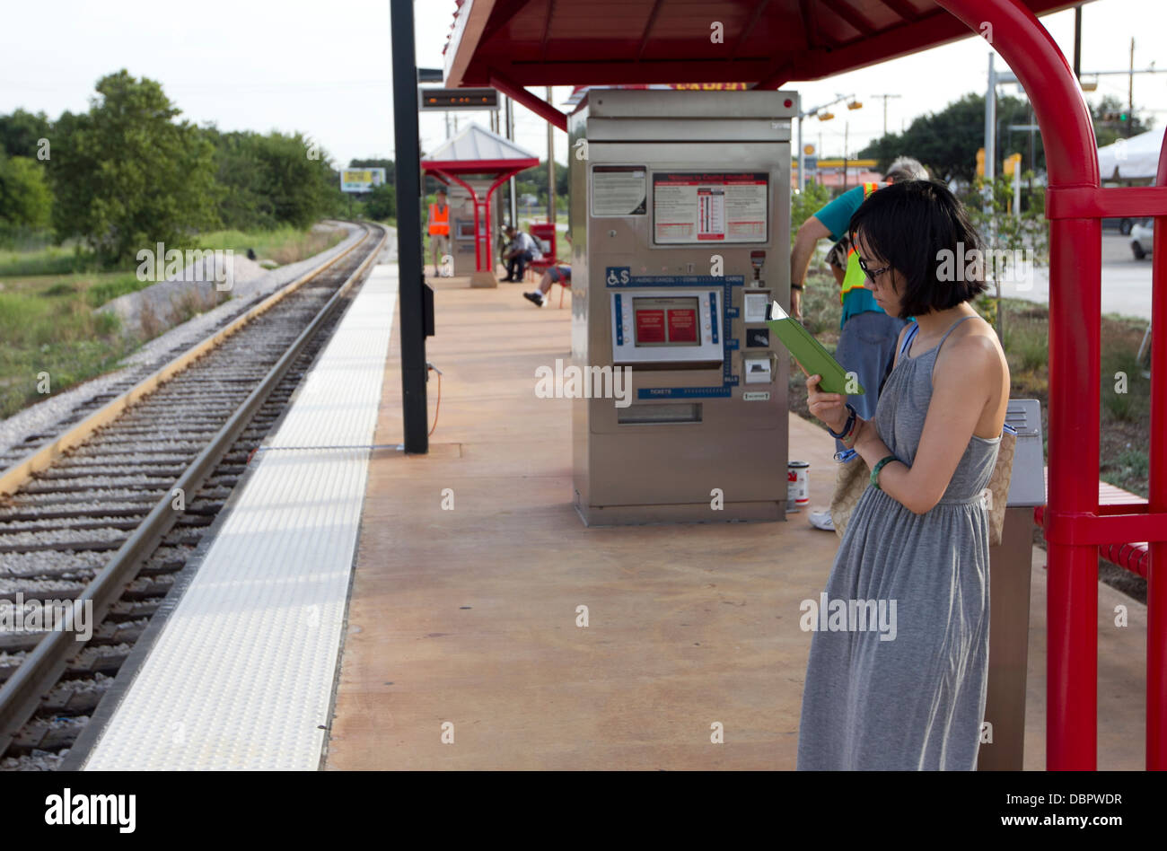 Woman reads on her ebook reader Kindle as she waits for a public transportation metro rail train on her morning - Stock Image
