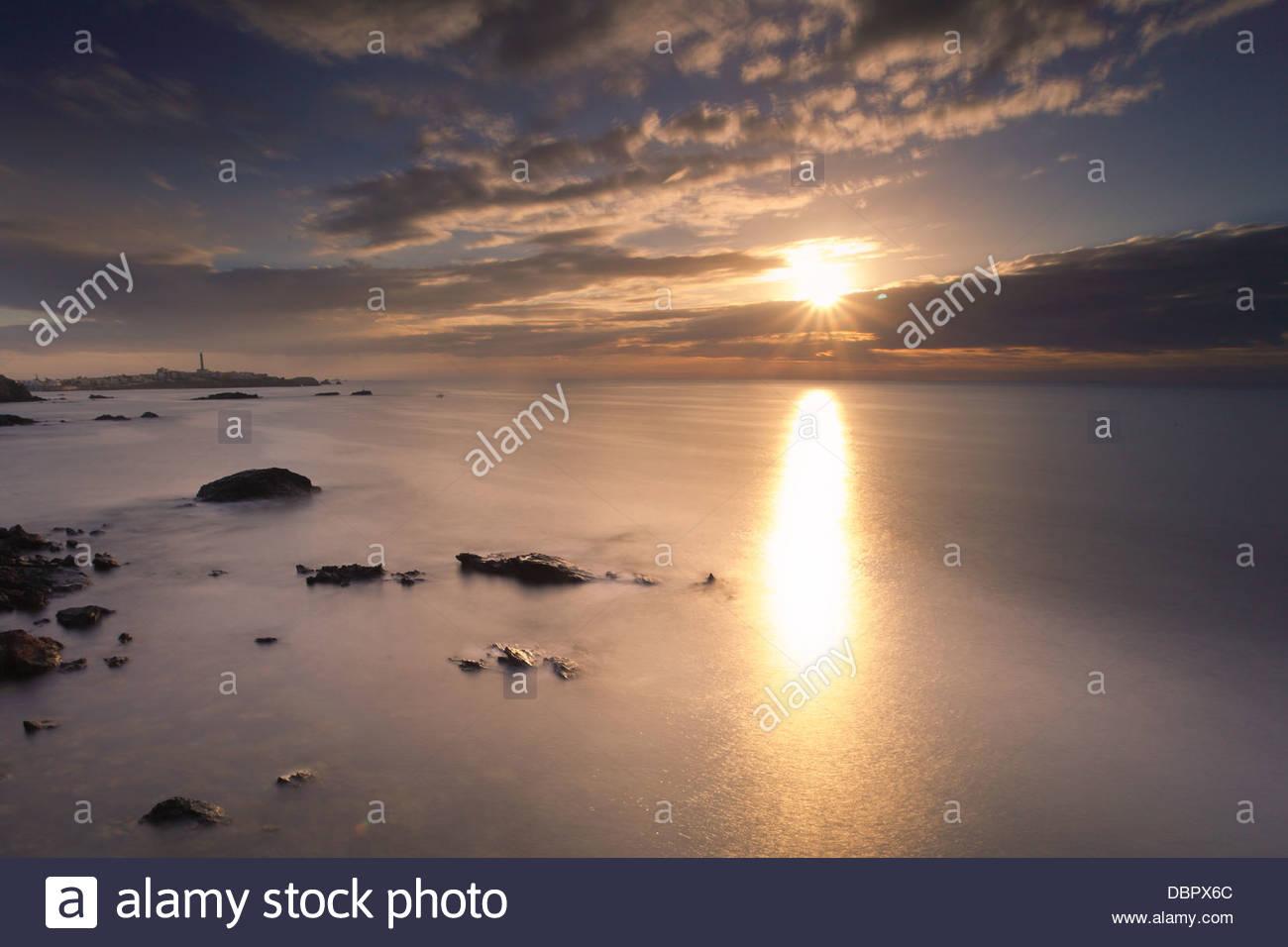 Rising sun at the ocean - Stock Image