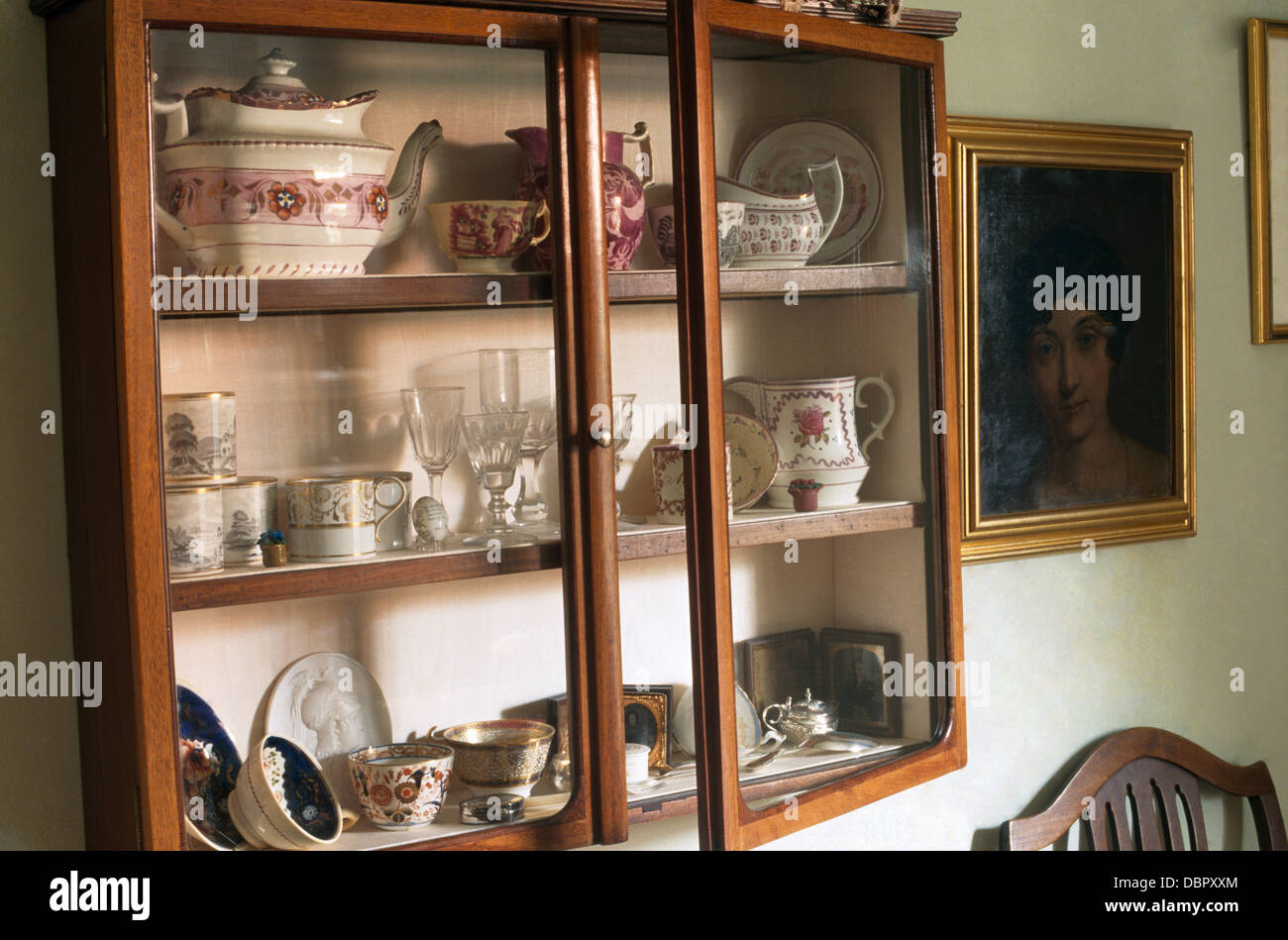 Close-up of antique china on shelves in old wall cupboard with glass doors - Close-up Of Antique China On Shelves In Old Wall Cupboard With Glass