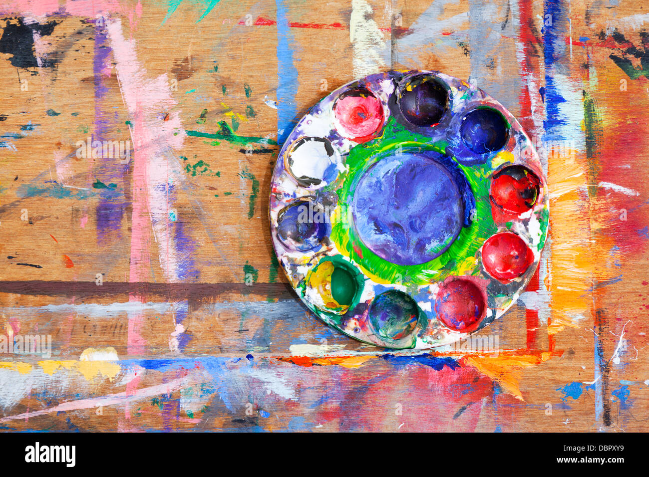 Close-up of a multi-coloured plastic paint palette on a paint splashed wooden board. - Stock Image