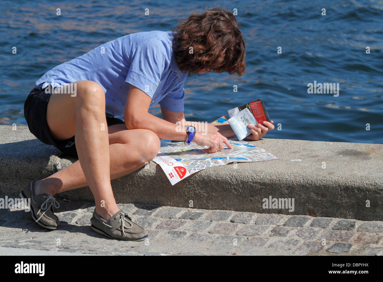 Female tourist studying the Copenhagen city map on the jetty near the Royal Playhouse in the port of Copenhagen. - Stock Image