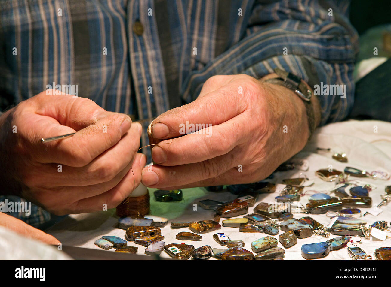 Artisan works with stone gems, close up of hands - Stock Image