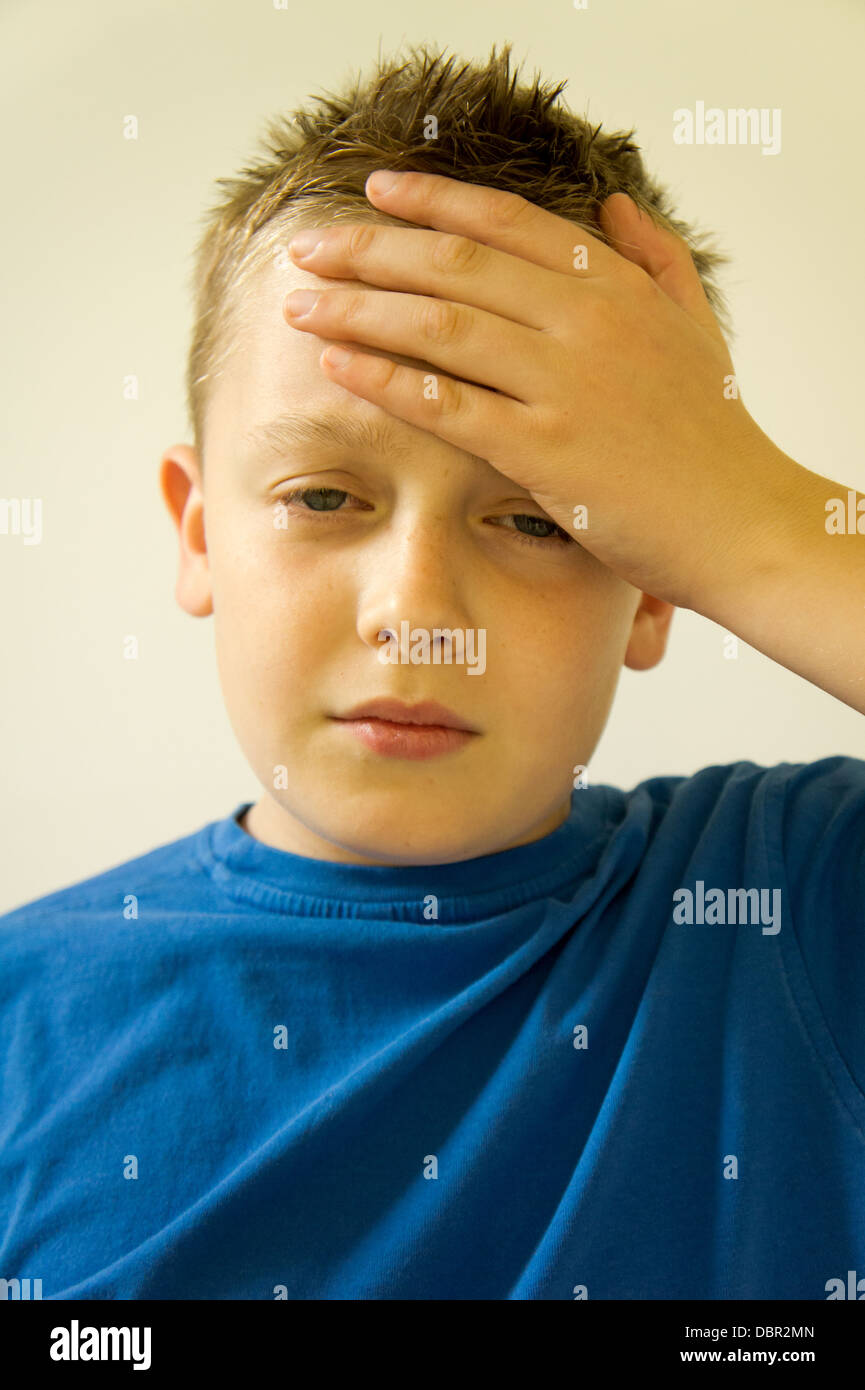 Boy holding his hand to his head with a headache - Stock Image
